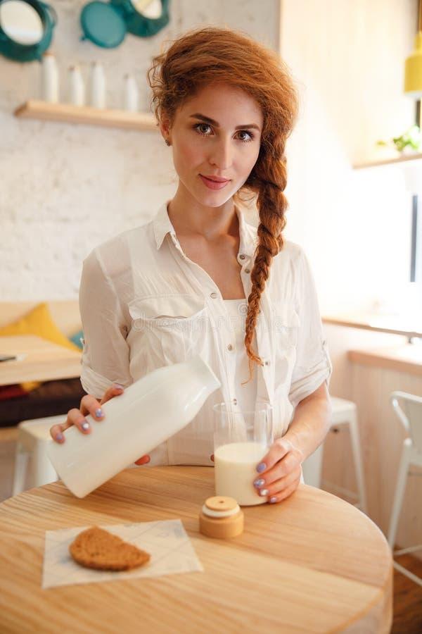 Auslaufende Milch der recht roten behaarten Frau im Glas von der Flasche lizenzfreies stockfoto