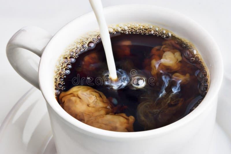 Auslaufende Sahne in einen Kaffee stockfotografie