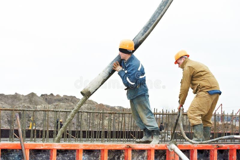 Auslaufender Beton der Erbauerarbeitskraft in Formular stockfoto