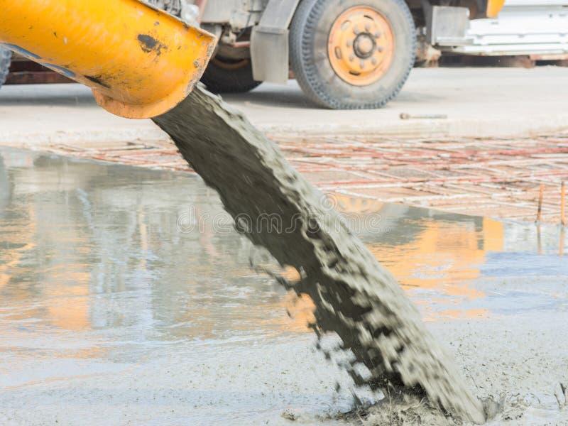 Auslaufender Frischbeton nach der Platzierung der Stahlverstärkung, um die Straße durch das Mischen des Mobiles herzustellen der  lizenzfreie stockfotos