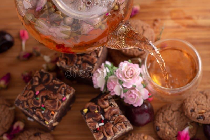 Auslaufender Kräutertee von der Teekanne in Glasteeschale mit Schokoladenkuchenstapel backen auf dem Holztisch zusammen stockfotos