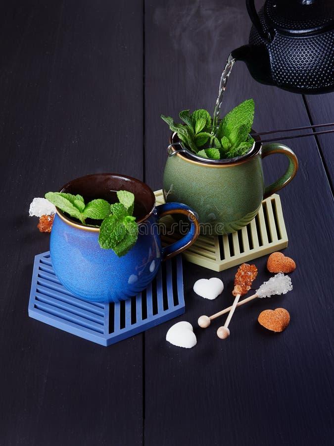 Auslaufender tadelloser Tee von einer schwarzen Roheisenteekanne über einem Sieb mit frischen tadellosen Blättern lizenzfreies stockbild