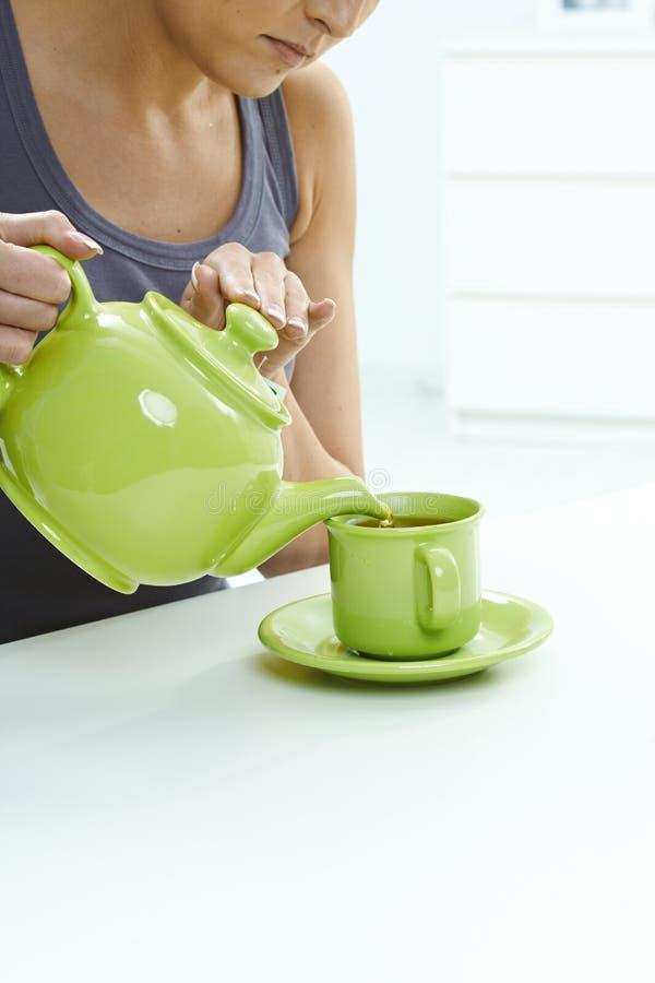 Auslaufender Tee der Frau vom Kessel, zum auf Tabelle zu überfallen stockbilder