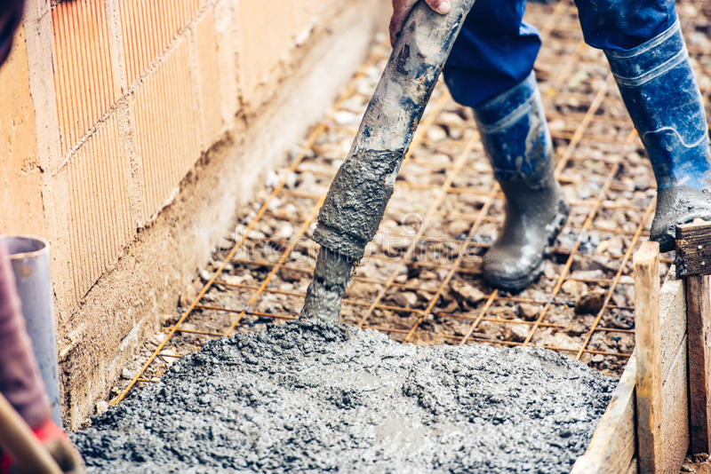 Auslaufender Zement oder Beton des Industriearbeiters mit automatischem Pumpenrohr stockfotos