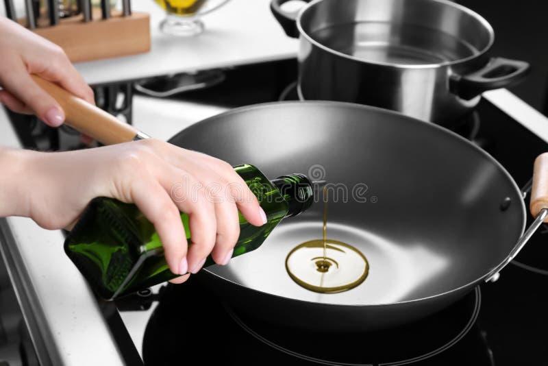 Auslaufendes Öl der Frau von der Flasche auf Wok stockbilder