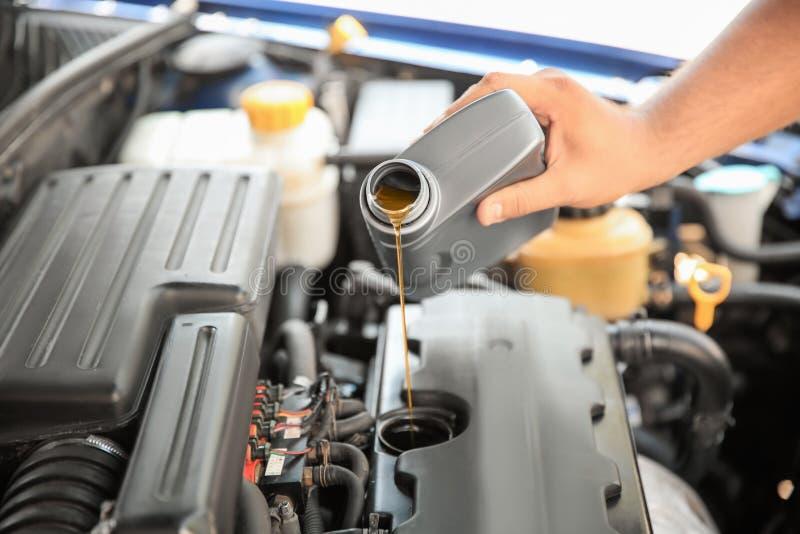 Auslaufendes Öl des Mechanikers in Automotor lizenzfreie stockfotografie
