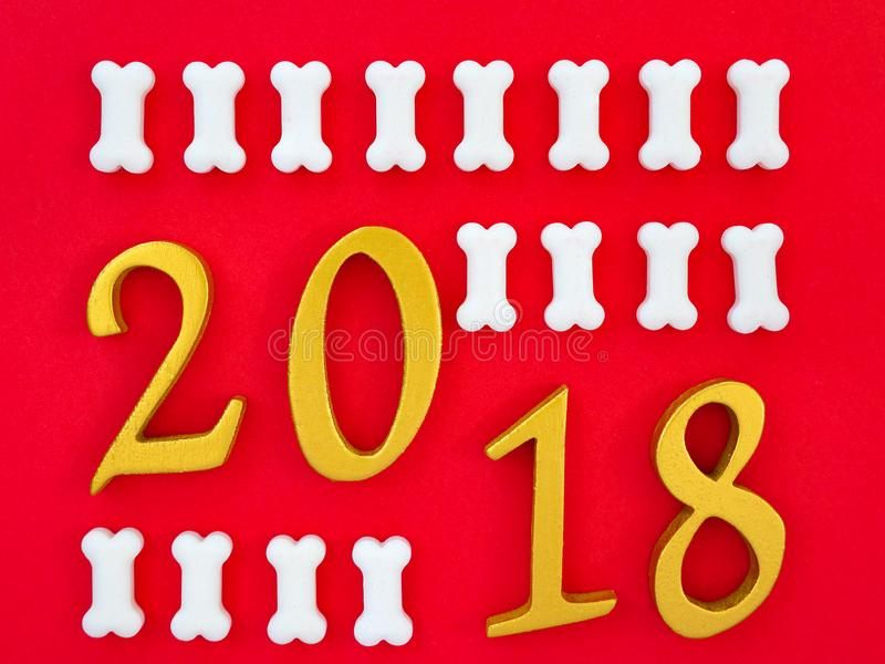 Auspicious new year 2018. An image of number 2018 in gold with white pieces of dog treats on bright red background, symbolizing auspicious new year 2018, Year of royalty free stock image