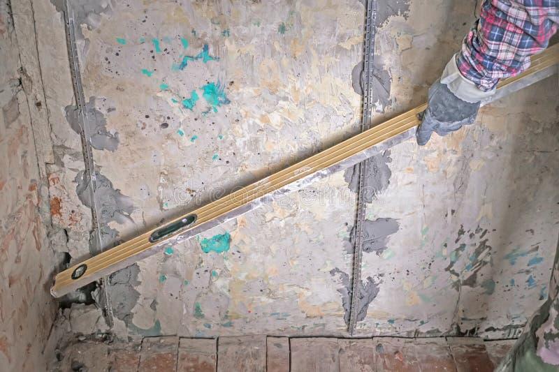 Ausrichtung von Wänden in der Reparatur mithilfe einer speziellen Geräteebene Abschluss oben stockfotografie