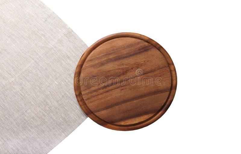 Ausschnitt-Pizzabrett Browns rundes für Feiertagsteller auf der grauen Leinenserviette lokalisiert auf Weiß Draufsicht und Spott  lizenzfreie stockfotografie