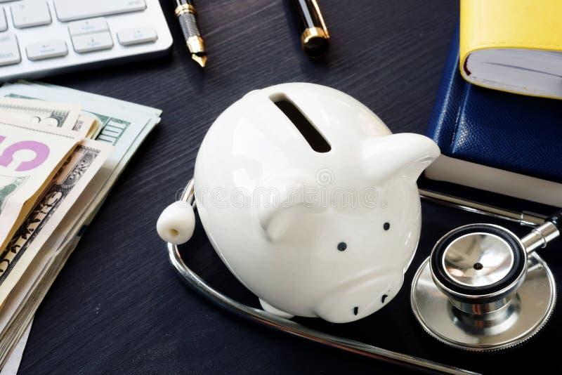 Ausschnittspfad eingeschlossen Stethoskop und piggy Querneigung lizenzfreies stockfoto