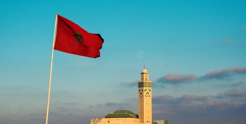 Aussicht auf die berühmte Hassan-II-Moschee und eine steigende marokkanische Flagge stockbild