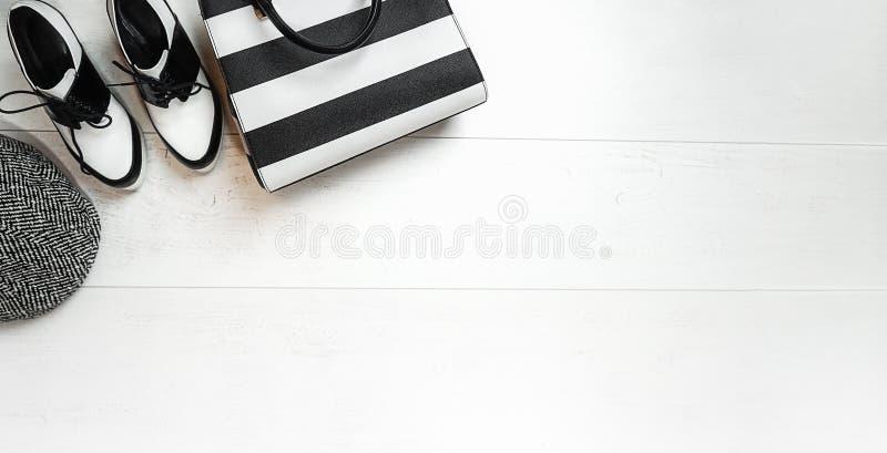 Ausstattungssammlungskleiderschwarzweiss-Schuhkappen-Taschenzusätze der Draufsicht weibliches auf weißem hölzernem Hintergrund Va stockbild