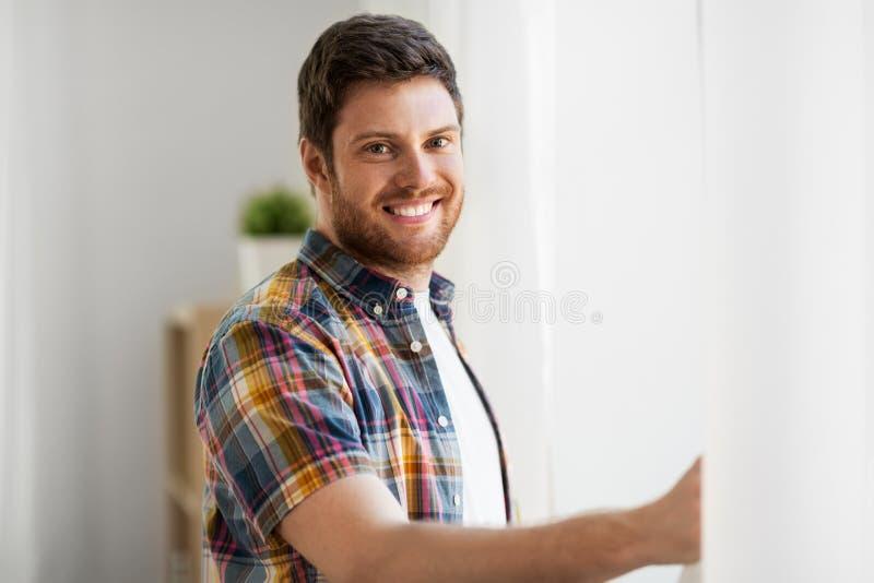 Ausstellfenstervorhang des jungen Mannes zu Hause stockfotos
