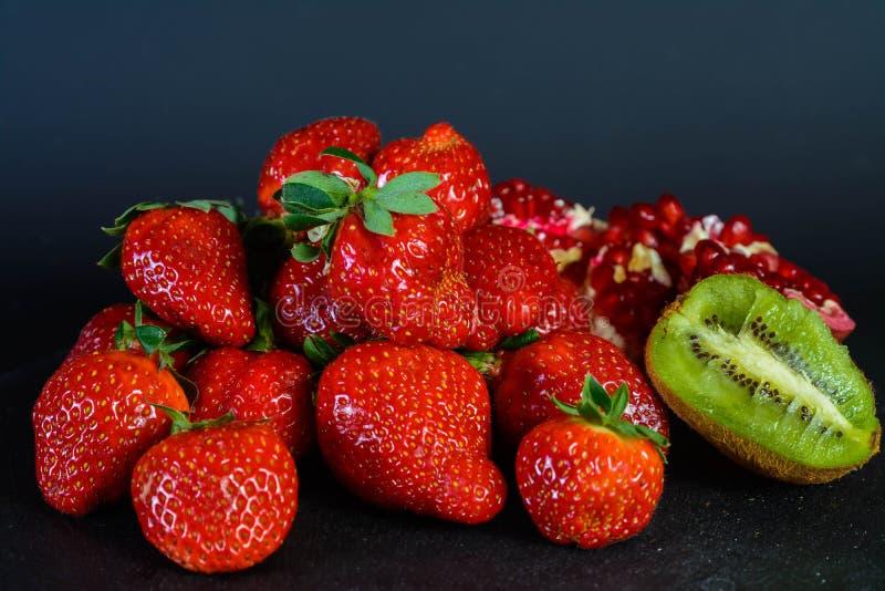 Ausstellung der frischen organischen Erdbeere, Hälfte des Granats und Kiwi auf schwarzem Hintergrund lizenzfreie stockfotos