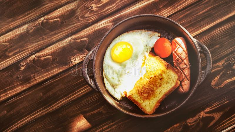 Austere and modest Breakfast. Scrambled eggs, toast and fried sausage in a cramped clay plate on an old wooden table. royalty free stock photos