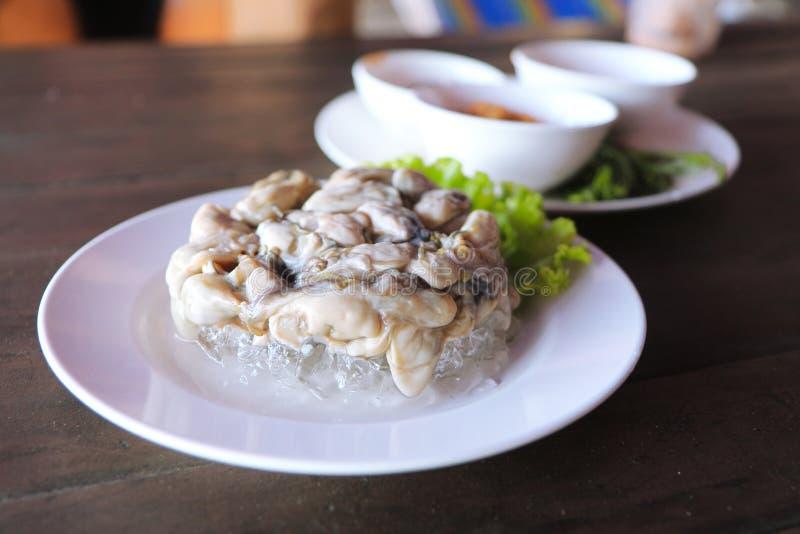 Austern sind Meeresfrüchte Es ist rohes Fleisch von Austern Gedient auf Eis, Gemüse, würzige Soße, Leucaena, Schalotten lizenzfreie stockbilder