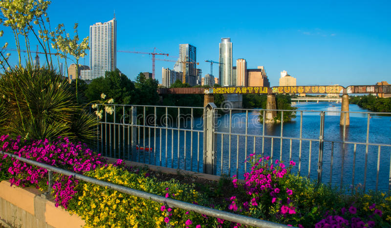 Austin Texas Growing City with Cranes and Colorful Flowers on bridge Over Town Lake. With Towers and tall skyscrapers the Austin Cityscape royalty free stock photo