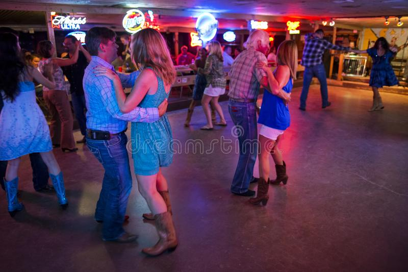 People dancing country music in the Broken Spoke dance hall in Austin, Texas. Austin, Texas - June 13, 2014: People dancing country music in the Broken Spoke stock images