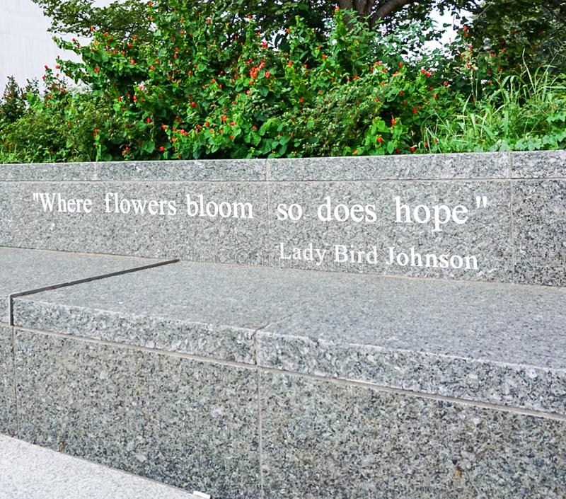 AUSTIN TEXAS- SEPTEMBER 17, 2017:Quote: `Where flowers bloom so does hope` by Lady Bird Johnson on a bench outside The Lyndon B. Quote: `Where flowers bloom so stock images