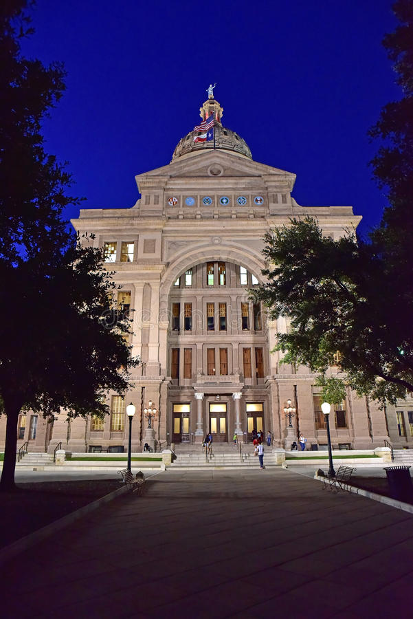 Austin.Texas in United States of America - August 2015.Texas par. Liament building in the evening, the illuminated front.At the top of the building waving two stock photos