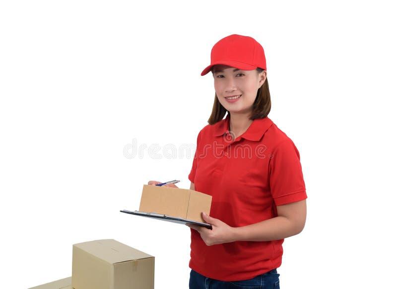 Austrägerin in der roten Uniform mit den Paketkästen, die Anmerkungen auf dem Lieferungsempfangsklemmbrett, lokalisiert auf Weiß  stockbild