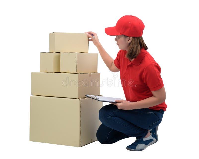 Austrägerin in der roten Uniform mit den Paketkästen, die Anmerkungen auf dem Lieferungsempfangsklemmbrett, lokalisiert auf Weiß  stockfoto