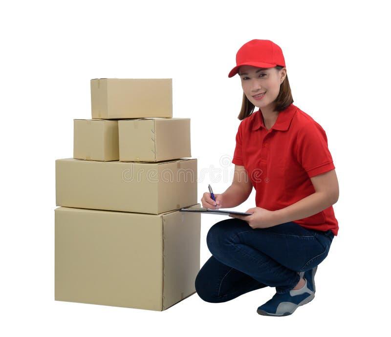 Austrägerin in der roten Uniform mit den Paketkästen, die Anmerkungen auf dem Lieferungsempfangsklemmbrett, lokalisiert auf Weiß  lizenzfreie stockfotografie