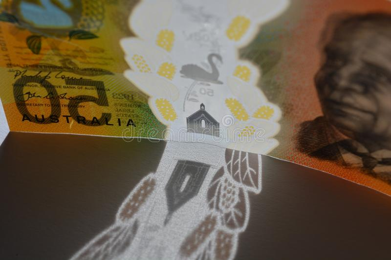 Australia $50 bill, backlit on a plain background. Australian fifty dollar note, standing on edge, backlit,  creating a shadow of the clear plastic security stock photography