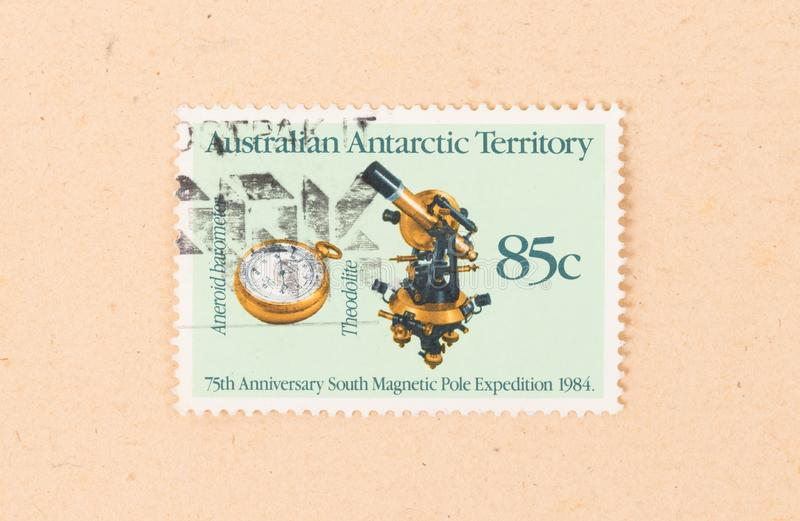 A stamp printed in Australia shows images of a theodolite and an aneroid barometer, circa 1990 royalty free stock photography