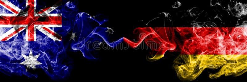 Australia contra Alemania, banderas místicas ahumadas alemanas colocadas de lado a lado Grueso coloreado sedoso fuma la combinaci foto de archivo