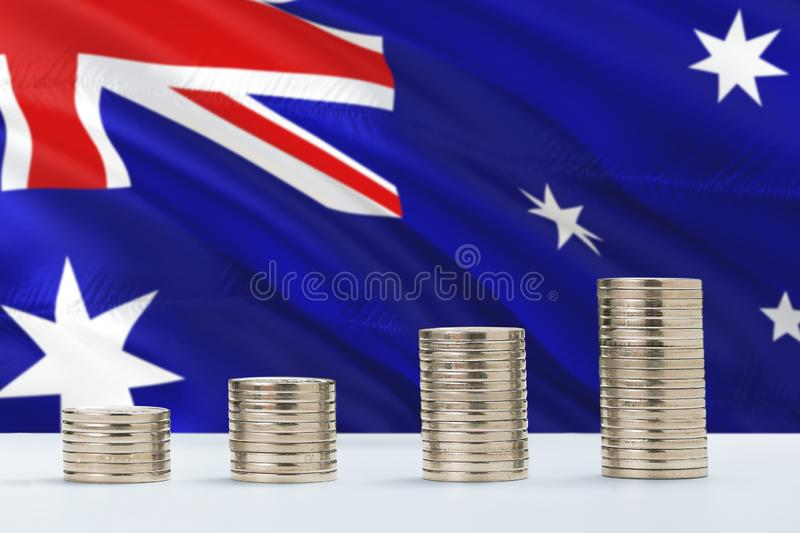 Australia flag waving in the background with rows of coins for finance and business concept. Saving money royalty free stock images