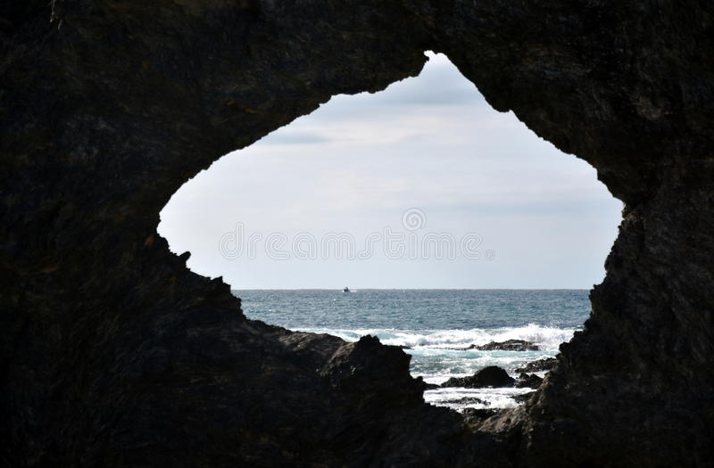 Australia rock and ocean in Narooma. The shape of Australia cut into the rock wall was accidental and was created when a ship was tied to the rock with large royalty free stock photo