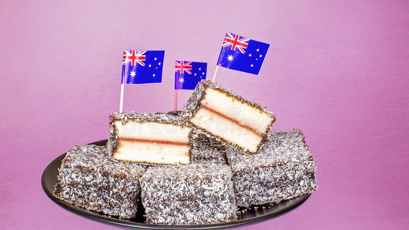 Australia`s Favorite Cakes With Flags. Traditional Australian lamingtons, individual cakes filled with jam, iced and rolled in coconut. Favorite food on royalty free stock image