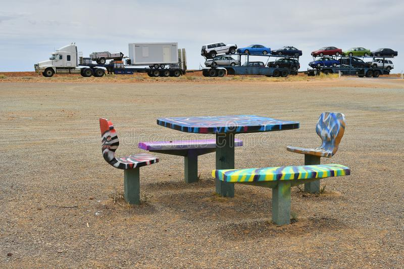 Australia, South Australia, transport and rest area. Pimba, SA, Australia - November 12, 2017: Colorful seating group on rest area and road train on Stuart royalty free stock image