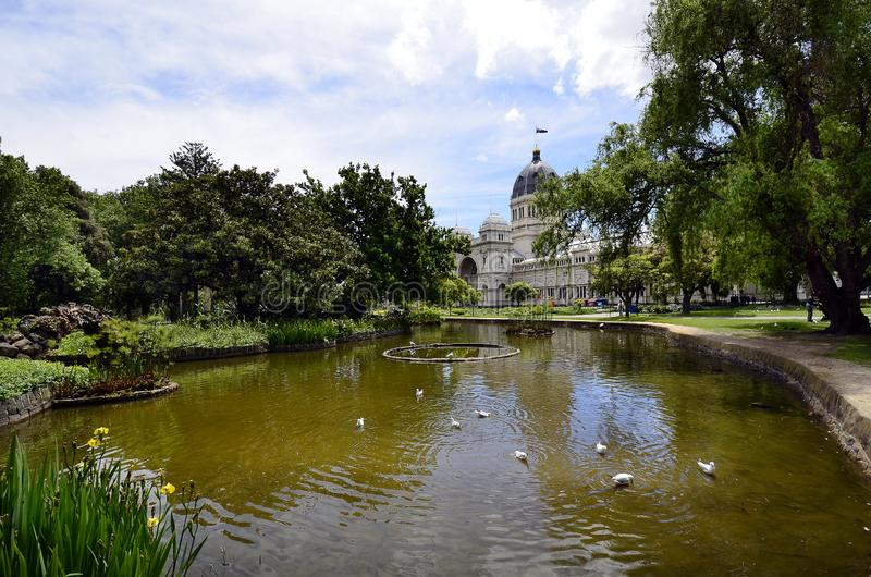 Australia, Victoria, Melbourne, Carlton Gardens. Melbourne, VIC, Australia - November 05, 2017: Pond with birds and Royal Exhibition building in public Carlton royalty free stock images