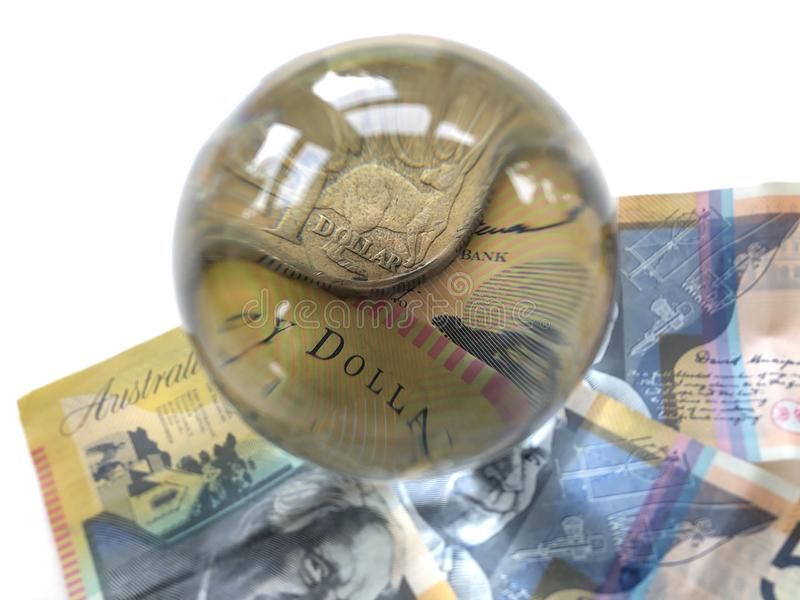 Australian banknotes, coin and a crystal ball. Australian $50 banknote and a $1 coin seen through a crystal ball. Predicting the futures market. Creative concept royalty free stock image