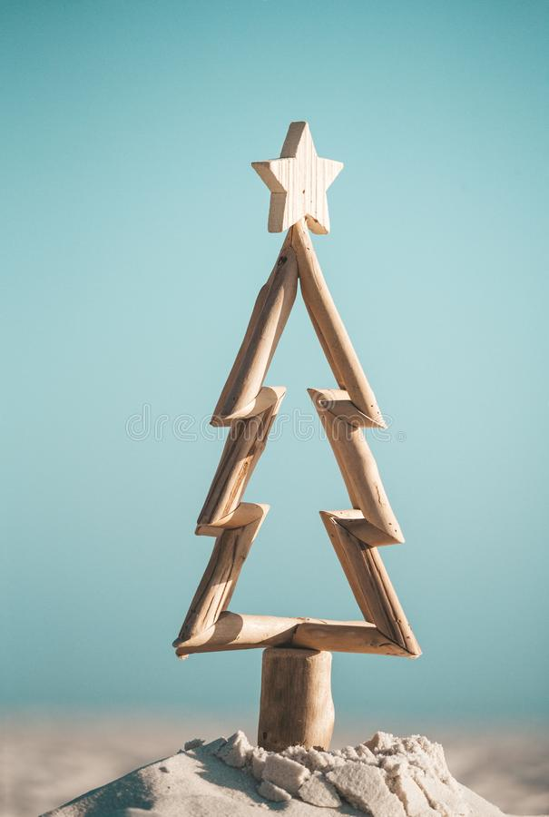 Australian Christmas. Driftwood timber Christmas tree in sand by the ocean stock image