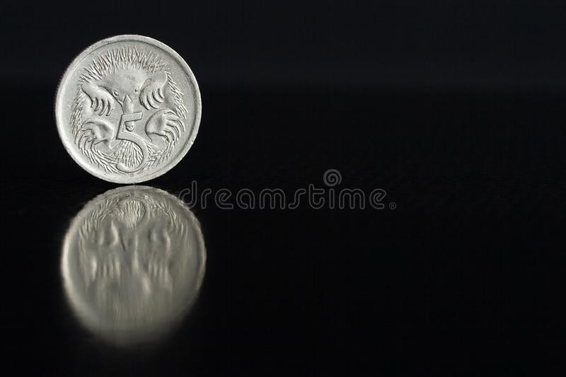 Australian coin five cents 1987 on the edge on black background with reflection. Australian silver coin five cents 1987 on the edge on black background with royalty free stock image