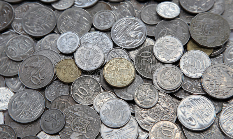 Australian coins. Various Australia coins in a pile. Focus on central gold coloured one dollar coin royalty free stock images