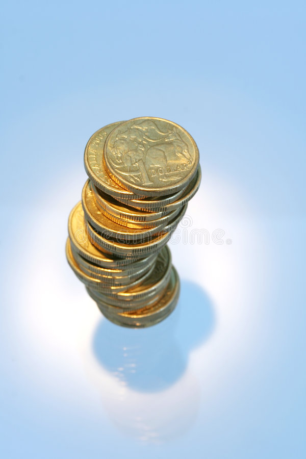 Australian Coins. Australian one dollar coins in a stack, spotlighted royalty free stock photo