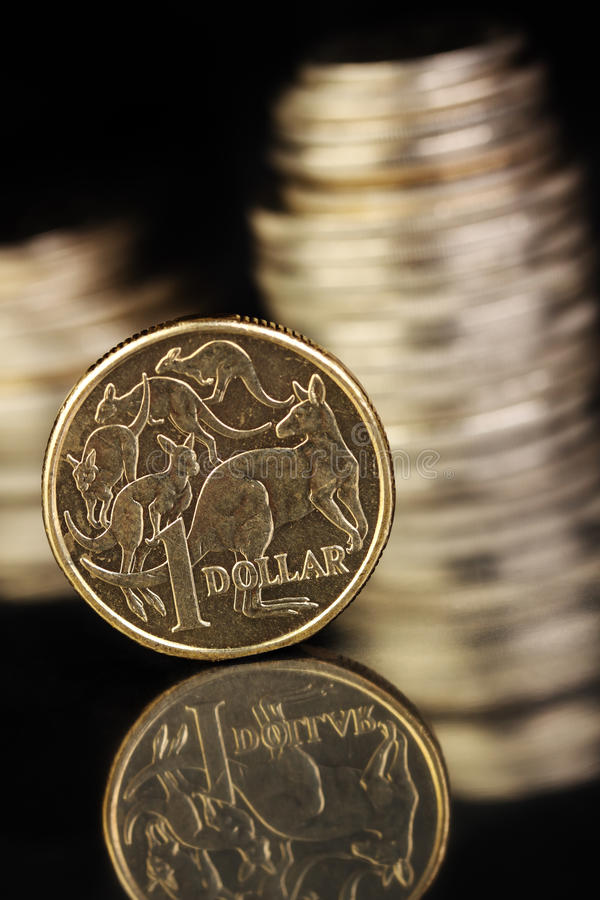 Australian currency. Australian $1 coin on a dark reflective surface. Various aussie coins in the background royalty free stock photography