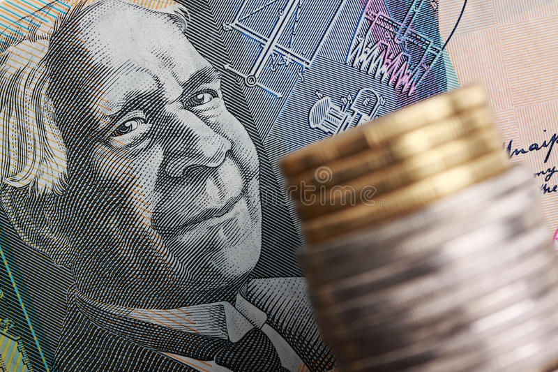Australian currency. Australian $50 note with coins stacked in foreground. Focus on the face of David Unaipon, aboriginal writer and inventor as he appears on stock photography