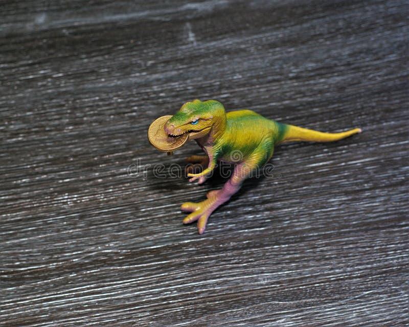 Australian dollar coin in dinosaur`s mouth. Rubber toy dinosaur on a table has an Australian one dollar coin in its mouth royalty free stock photography