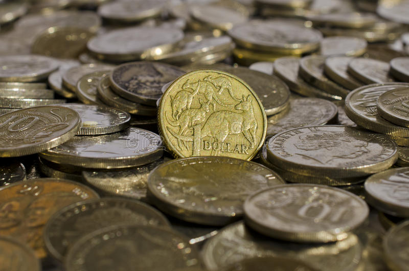 Australian Dollar Coin. An Australian $1 coin sits upright in a pile of five, ten and twenty cent coins stock photography
