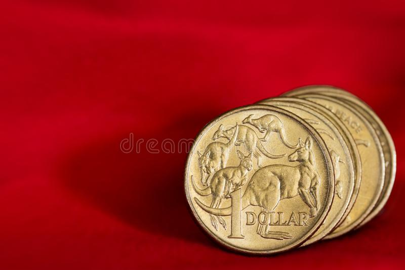 Australian Dollar Coins over Red Background. Australian one dollar coins over vibrant red background, with copyspace royalty free stock photo