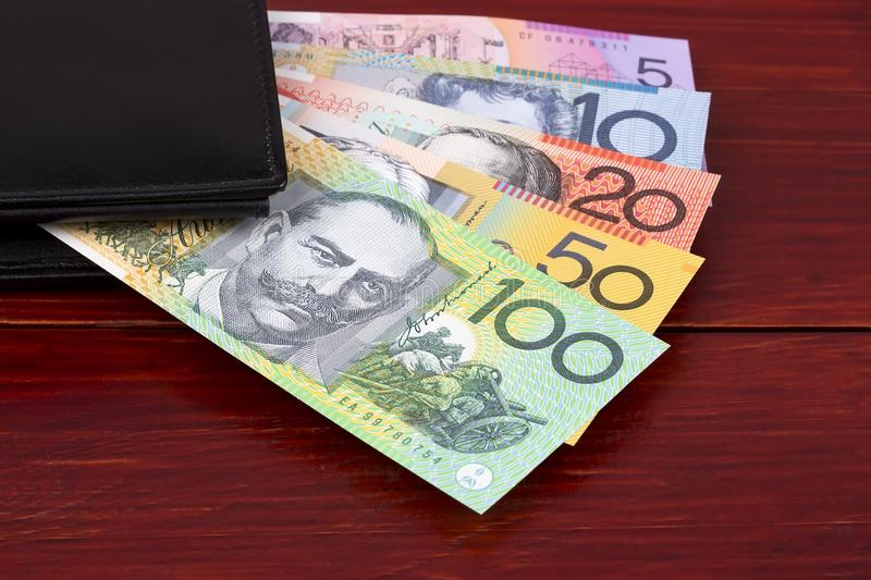 Australian Dollars in the black wallet. On a wooden background stock photography