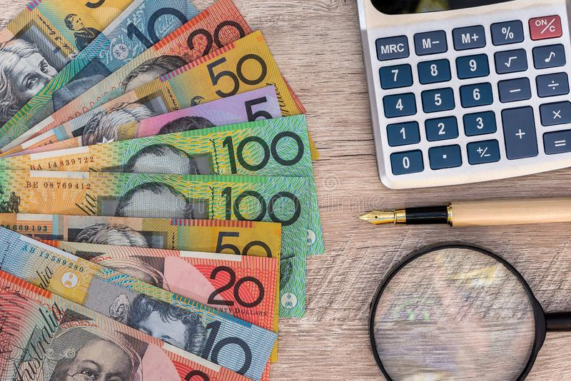Australian dollars with calculator, pen and magnifier.  stock image