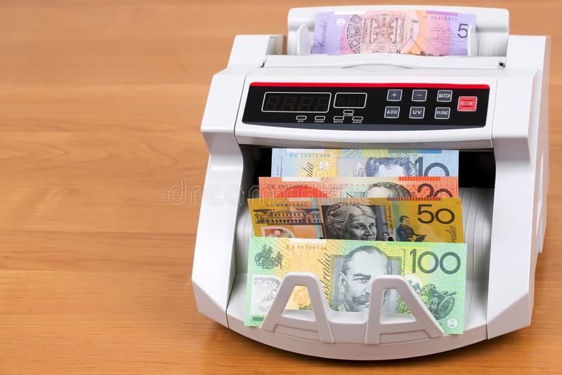 Australian Dollars in a counting machine. On a wooden background stock images