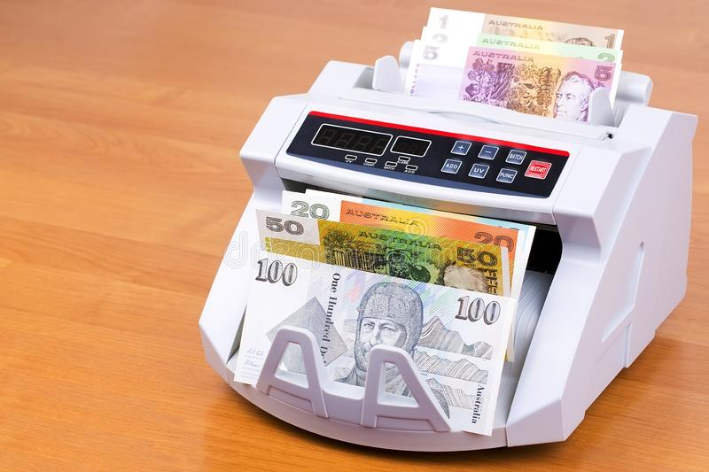 Australian Dollars in a counting machine. On a wooden background royalty free stock image