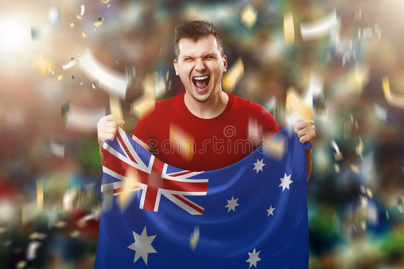Australian fan, a fan of a man holding the national flag of Australia in his hands. Soccer fan in the stadium. Mixed media royalty free stock photos